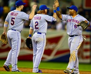 Mets players high-five one another after completing a Queens-Bronx sweep of the Yankees in this year's Subway Series.