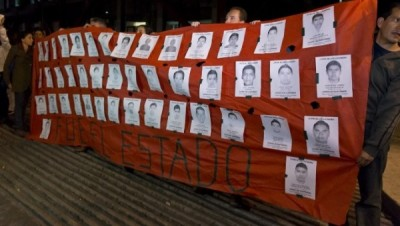 protesters_in_mexico_city_with_photos_of_the_43_missing_studentsx_with_it_was_the_state_written_on_the_banner._afp.jpg_1718483346